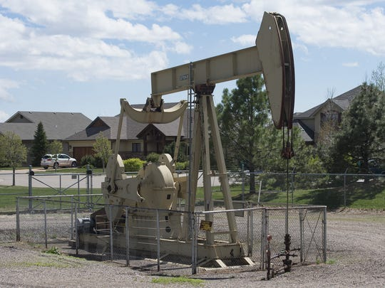 A pumpjack rig, used in oil extraction methods, is surrounded by homes in the Hearthfire neighborhood in north Fort Collins..