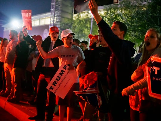 Donald Trump supporters yell at protesters across a