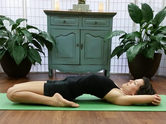 Aja Reeser demonstrates reclined Hero Pose at Yoga Bird, Fort Myers.
