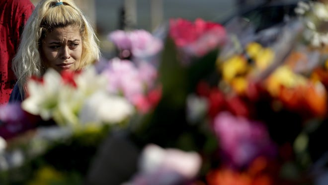 Sara Whithead looks at a makeshift memorial on the hood of car believed to belong to victims of a duck boat accident in the parking lot of the business running the boat tours Friday, July 20, 2018 in Branson, Mo. The country-and-western tourist town of Branson, Missouri, mourned Friday for more than a dozen sightseers who were killed when a duck boat capsized and sank in stormy weather in the deadliest such accident in almost two decades. (AP Photo/Charlie Riedel)