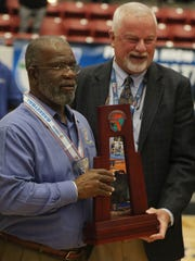 Rickards basketball coach Eli Bryant is awarded the Class 6A state runner-up trophy after a 71-62 loss to Leesburg on Friday night in Lakeland.