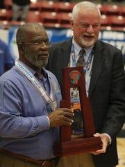 Rickards basketball coach Eli Bryant is awarded the