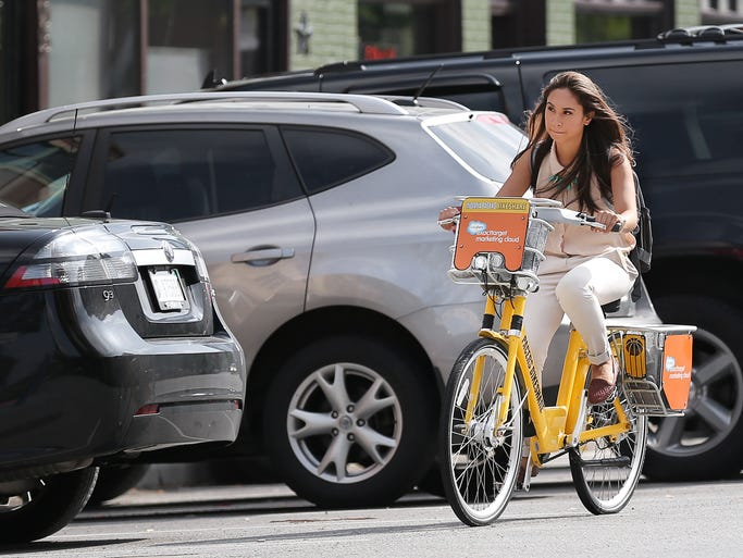 Camellia Beigh rides an Indy Bike Share bike back to her car on Massachusetts Avenue at the end of her work day in Indianapolis on Monday, June 30, 2014. Beigh is an employee of Exact Target who is paying for a full year membership to the program for those who use it.