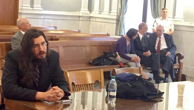 Michael Rotondo, left, sits during an eviction proceeding in Syracuse, N.Y., brought by his parents, Mark and Christina, of Camillus. The two parents confer with their lawyer, Anthony Adorante, in the court gallery behind. Rotondo told the judge Tuesday he knows his parents want him out of their Camillus home, near Syracuse. But he argued he's entitled to six months more time.