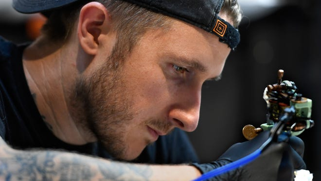 Tattoo artist Scott Campbell works on a client in his Saved Tattoo store in the Arts District of Los Angeles.