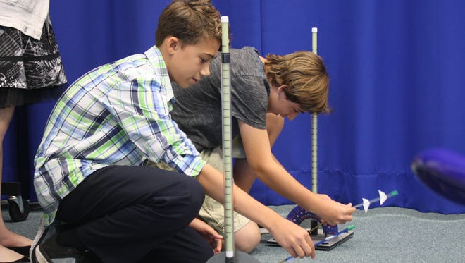 Students at Central Middle School in Melbourne launch rockets they built from straws, clay and paper during a STEM activity Thursday.
