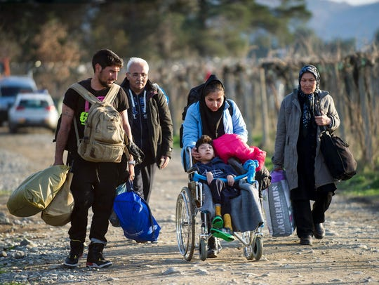 Migrants and refugees cross the Greek-Macedonian border
