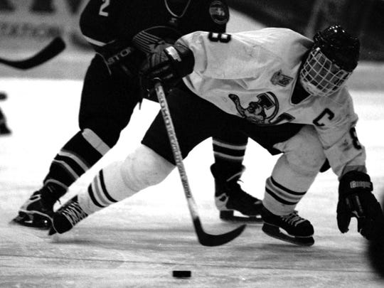 UVM's Martin St. Louis fights for control of the puck after getting shoved by Yale's Ray Giroux during the first period of an ECAC game at Gutterson Fieldhouse during the 1990s.