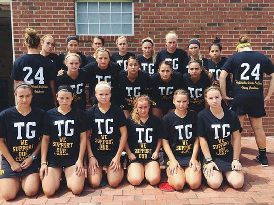 "Members of the University of Iowa field hockey team are pictured this past fall season wearing T-shirts with former coach Tracey Griesbaum's initials and ""We support our coach"" written on their fronts."