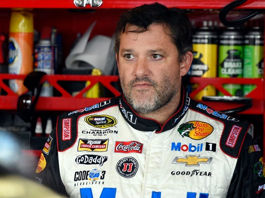 FILE - In this Sept. 13, 2014, file photo, NASCAR driver Tony Stewart (14) looks out from his garage during a practice for the NASCAR Sprint Cup Series auto race at Chicagoland Speedway in Joliet, Ill.