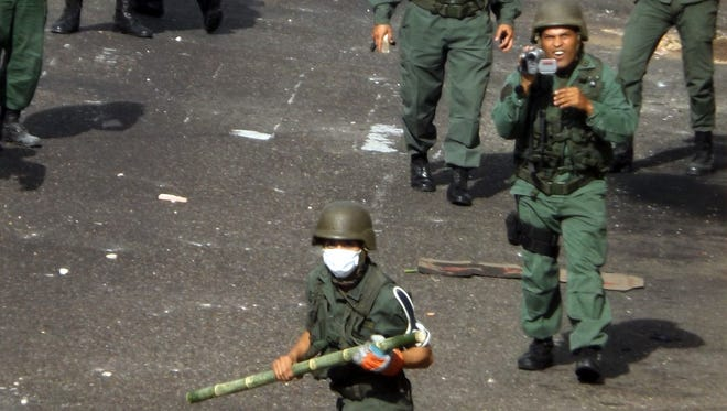 National Guard personnel face protesters in San Cristobal, capital of the western border state of Tachira, Venezuela, on Thursday.