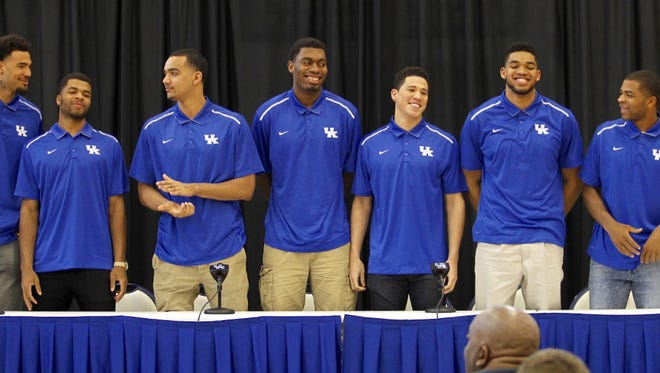 Kentucky's John Calipari smiles as players Willie Cauley-Stein, Andrew Harrison, Trey Lyles, Dakari Johnson, Devin Booker, Karl-Anthony Towns and Aaron Harrison stand to signal they are entering the NBA draft during a press conference at Joe Kraft Center in Lexington. By Matt Stone, The C-J April 9, 2015.