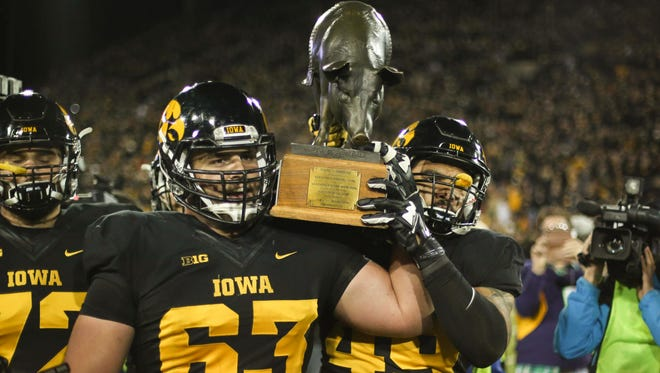 Iowa seniors Austin Blythe, left, and Melvin Spears carry the Floyd of Rosedale trophy after putting up a win over Minnesota on Saturday, Nov. 14, 2015, at Kinnick Stadium in Iowa City.