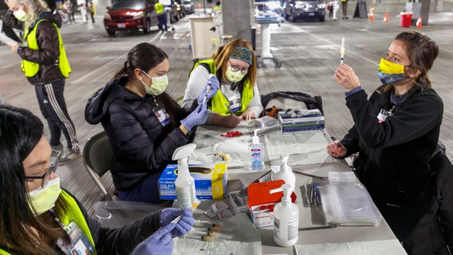 Medical professionals from Oregon Health & Science University load syringes with the Moderna COVID-19 vaccine at a drive-thru clinic in Portland, Ore., on Jan. 10. Oregon health officials and the state's vaccine advisory committee have made critical, often controversial decisions about which groups of people should be prioritized next for the vaccine amid limited supply.
