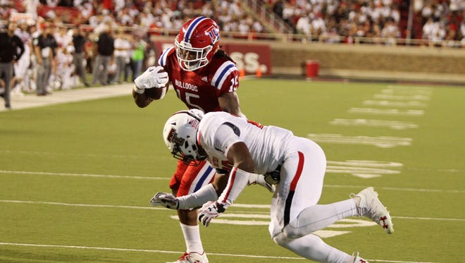 Louisiana Tech Bulldogs wide receiver Kam McKnight (15) rushes against Texas Tech Red Raiders defensive back Jordyn Brooks (20) in the second half at Jones AT&T Stadium. Texas Tech defeated Louisiana Tech 59-45.