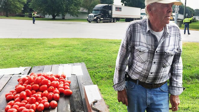 Cliff Greenup checks traffic at the intersection of U.S. 231 and Indiana 28, where he has a produce stand in Romney. He said traffic is up in Romney since the I-65 detour started Aug. 7. But business is down, he said, because no one wants to get out of line.