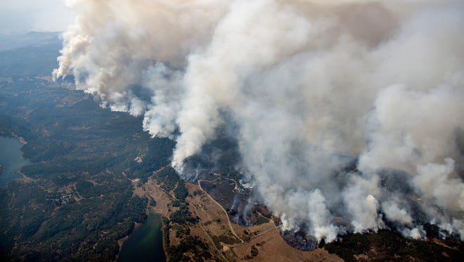 Smoke rises as a wildfire burns in the hills north east of Napa, Calif.