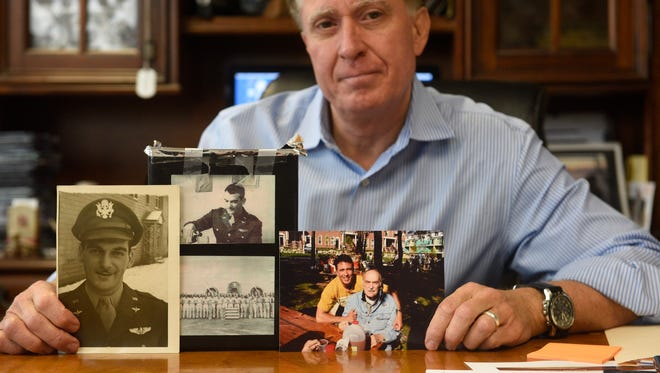 Keith Famie poses in his office with the ashes and photos of his dad who died from Alzheimer's.