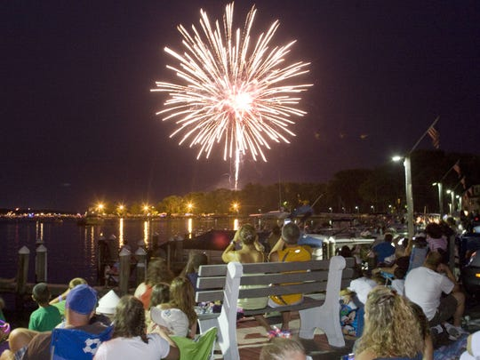 Fireworks erupt over the Toms River while viewers watch from the beach in Beachwood.