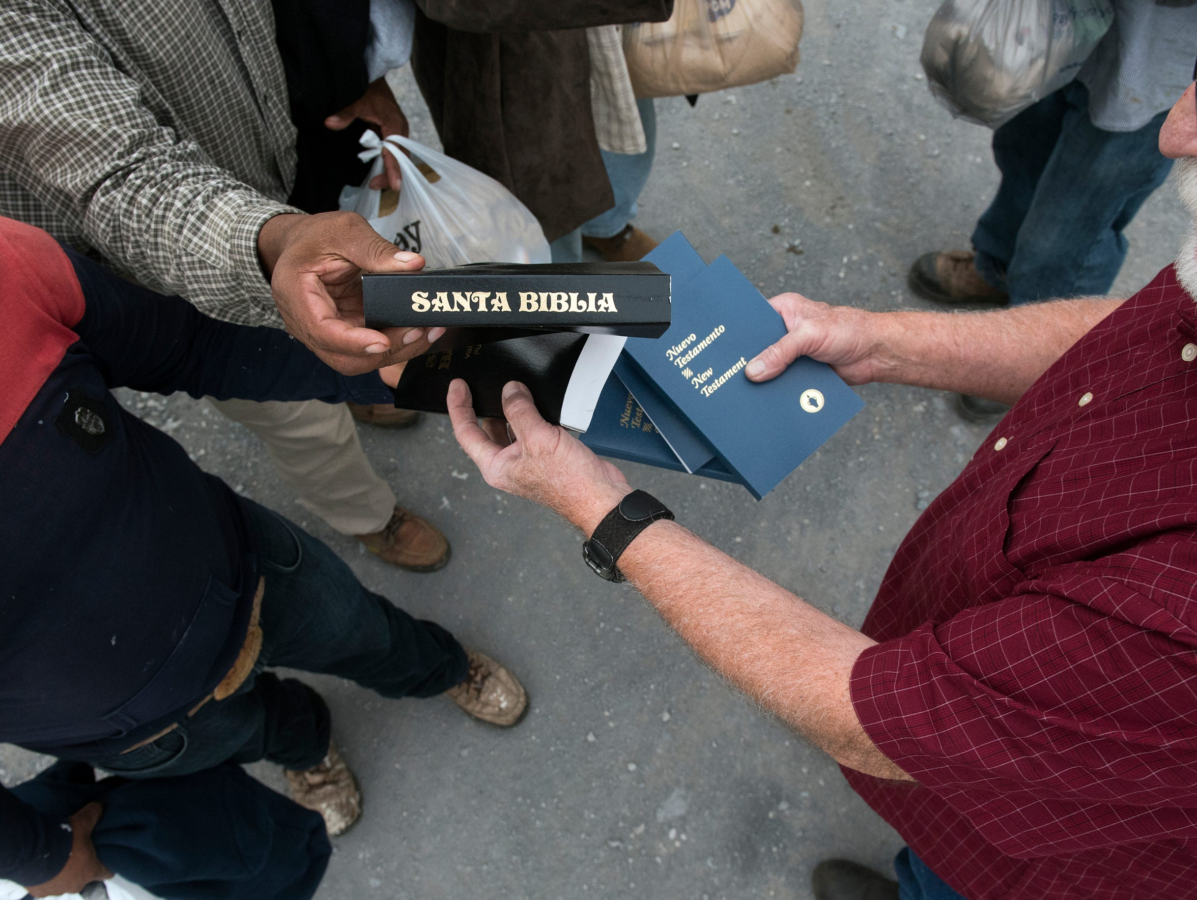 Runyan, right, hands out bibles to migrant workers,