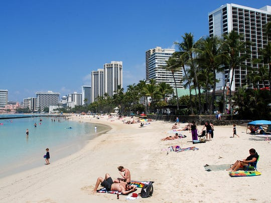 People relax on the beach in Waikiki in Honolulu. Many