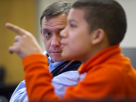 """Central Academy student Caden Carter, 13, explains the contingencies of the health insurance industry to his shadow, Henderson County High School Principal Chad Thompson, Wednesday morning. Thompson was taking part in the """"Shadow a Student Challenge"""" created by Stanford University's School of Design."""