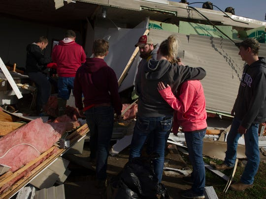 Jackie Thorne, second right, looks for support from her friend, Andrea Bromm, as friends and neighbors help remove belongings from her Fort Branch, Ind., mobile home Wednesday morning.