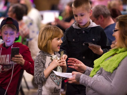 Adrianna, 5, and her mom, Tara Eckiss of Boonville, Ind., right, celebrate winning one of the night's drawings at the Tri-State Wrestling event at the Vincennes Eagles Lodge Saturday night. Adrianna's dad, Terry Joe Eckiss Jr., is a wrestler for the TSW.