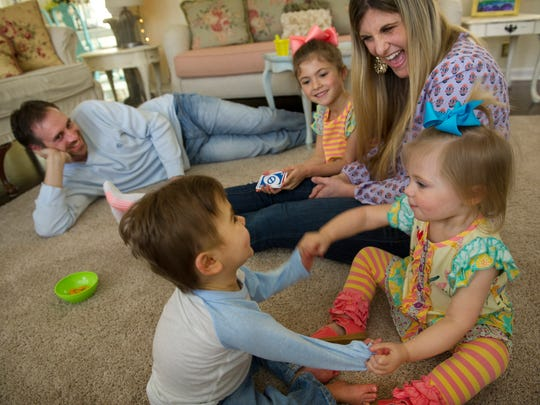 Luke Chapman, bottom left, and his twin sister, Kate, both 23 months old, play pat-a-cake during a morning round of Uno with dad Shawn, sister Avi, 6, and mom Jamie  Wednesday morning.