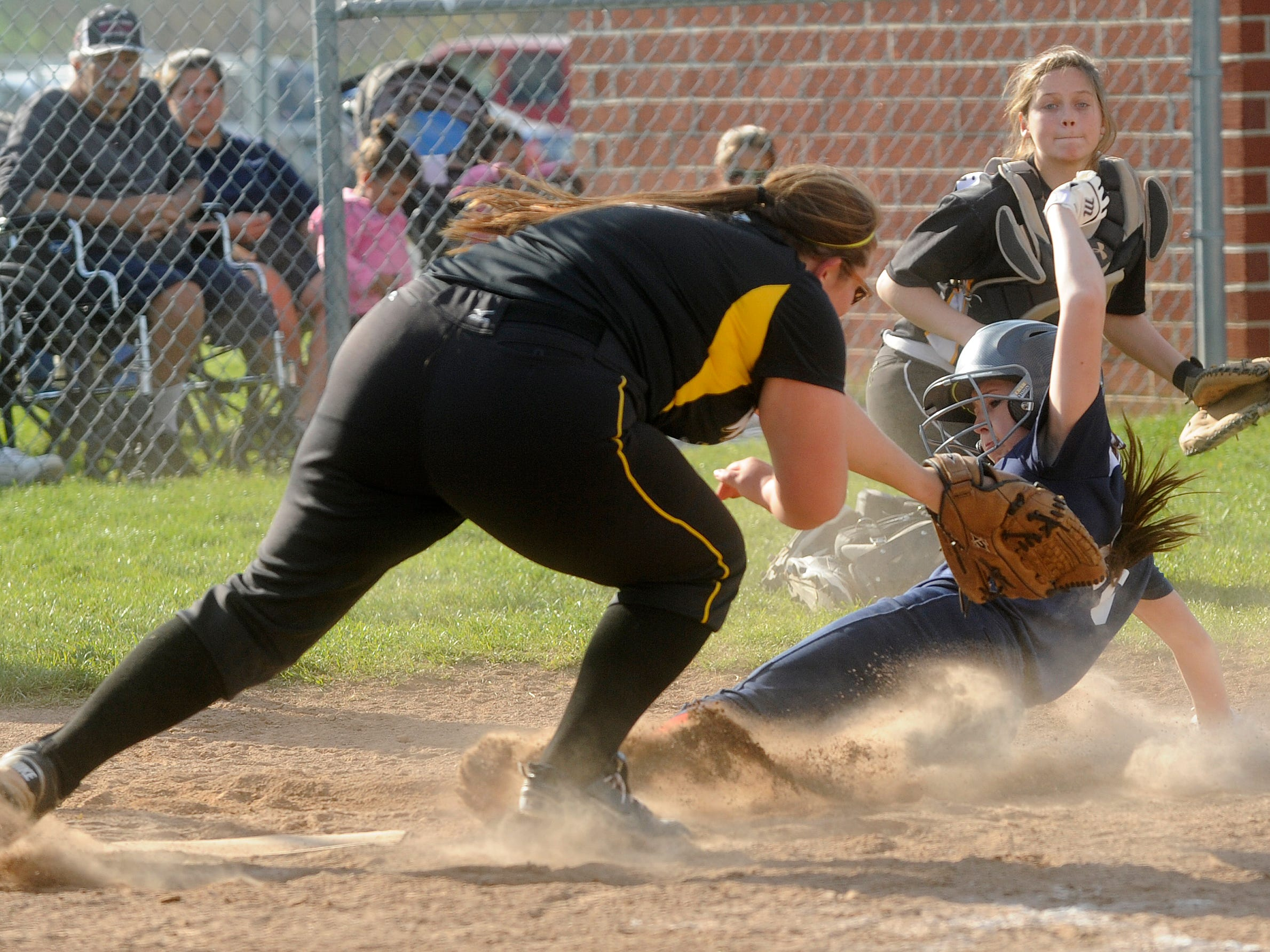 Licking Valley's Payton Brownlee slides safely into home while Watkins Memorial pitcher Emmalea Fuchs attempts to catch Miranda Warner's throw after a wild pitch. The Panthers defeated the Warriors 13-7 on Wednesday.