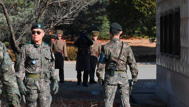 North Korean soldiers stare at South Korean soldiers at the truce village of Panmunjom in the Demilitarized Zone dividing the two Koreas on Nov. 27, 2017.