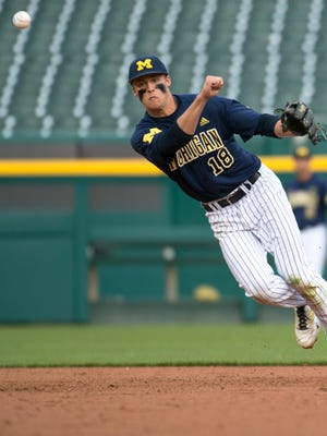Jake Bivens (18) short stop for the Michigan Wolverines throws to first in game action Tuesday night