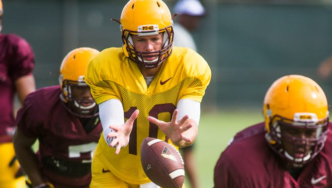 Quarterback Taylor Kelly takes a snap during ASU's practice on Aug. 22, 2014.