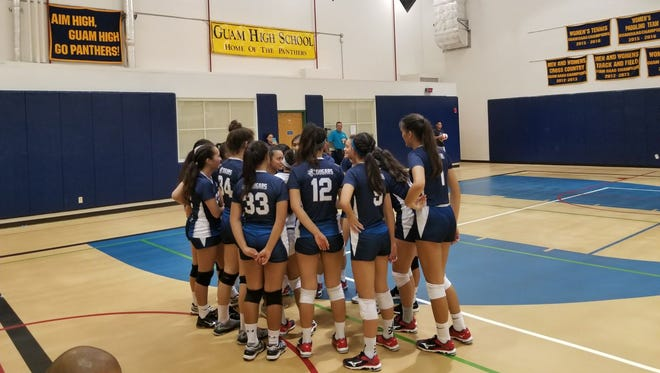 Cougars talk during a timeout in the second set. Academy leads Guam High 11-6 on Tuesday night.