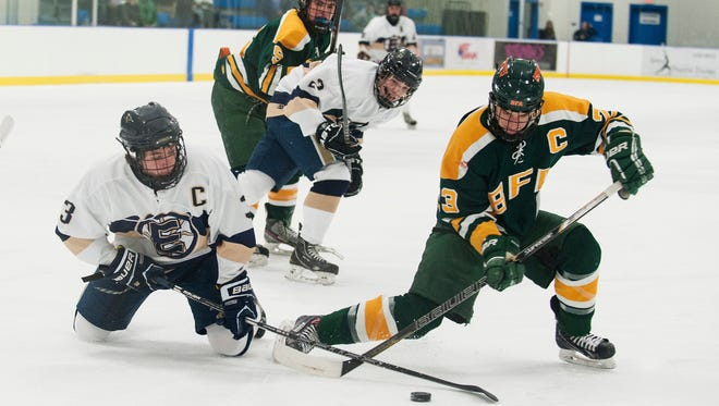 Essex's Brendan Gleason (3) and BFA-St. Albans' Peter Dukas (23) battle for the puck during the boys hockey game  at Essex High School on Dec. 13, 2014.