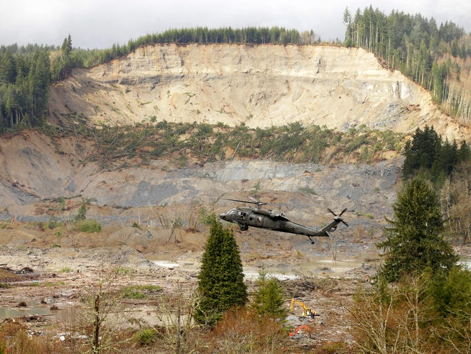 A military helicopter flies over mud and debris from the massive mudslide.