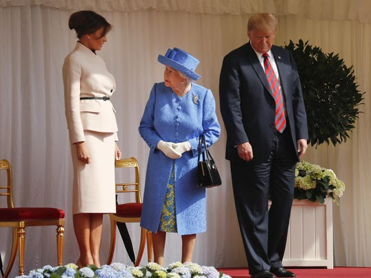 Queen Elizabeth II looks over towards first lady Melania