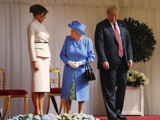 Queen Elizabeth II looks over towards first lady Melania