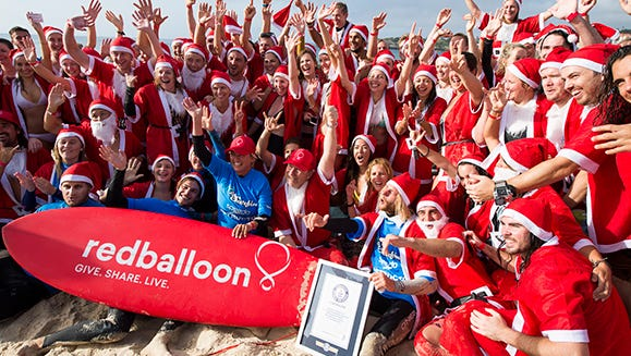 Guinness World Records adjudicator Solvej Malouf was on hand to congratulate participants for the world's largest surfing lesson on Dec. 15 on Bondi Beach, Australia. They're also, unofficially, claiming it's the world's largest Surfing Santa event.