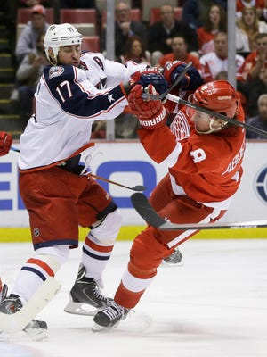 Columbus Blue Jackets center Brandon Dubinsky (17) checks Detroit Red Wings winger Justin Abdelkader during the second period of an NHL hockey game in Detroit, Tuesday, Dec. 16, 2014.