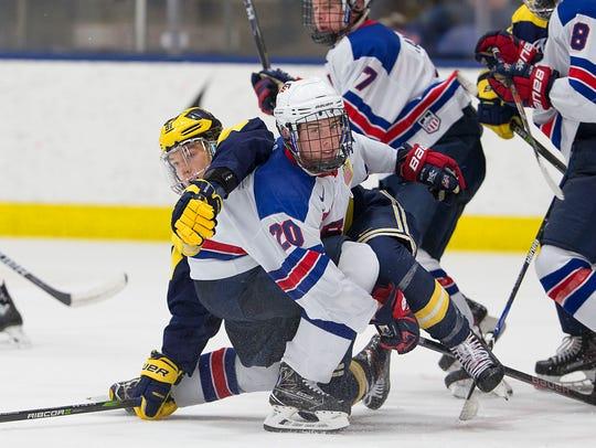 Team USA's Jake Pivonka (20) tries to keep the puck