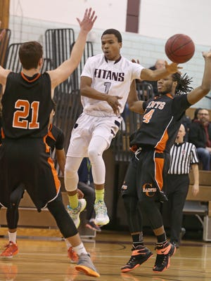Arcadia's Reggie Clark, center, draws in a trio of Churchville-Chili defenders including Myles McKinney, right, Andrew Kerwin, left, and Eric Lewis, then dishes off to teammate Eric Lewis for two during their game at Greece Monday, Jan. 11, 2016.