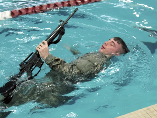 ROTC cadet Benjamin Drapeaux carries a rifle during a training exercise in the pool at Norwich University in Northfield.