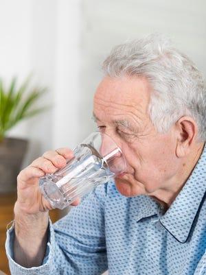 A man in pajamas drinking water