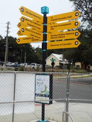 A wayfaring sign at the Smokey Hollow Commemoration points to other attractions in Cascades Park.