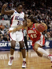 Jeomi Maduka is pictured driving against Connecticut's Tina Charles during the first half of their NCAA tournament game in 2008. Maduka was chosen as the top female athlete in Cornell history by a panel that included Cornell graduates and staff members as well as media. The panel ranked the top 20 men and top 10 women.