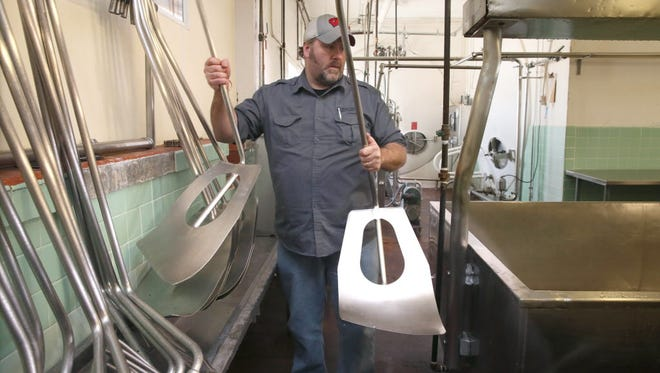 Jay Noble moves some cheese agitators into place. Noble and his brother John are restarting the Beechwood cheese plant near Adell, in Sheboygan County.