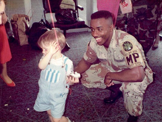 """A child greets Olaudah Parker at Fort Hood, Texas, as he returns home from Desert Storm. Hundreds of people were there to greet their arrival. """"This kid wanted to shake my hand but when I stooped down to shake his hand he turned away. He came back later to shake my hand,"""" he said."""