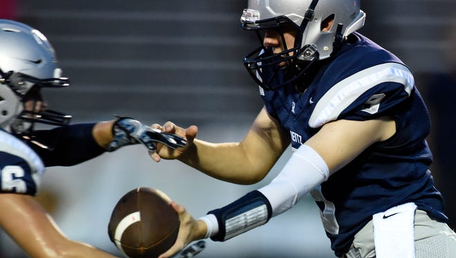 Reitz quarterback Reid Mahan hands the football off to Noah Jones while going up against the Central defense during the first quarter of the game at the Reitz Bowl in Evansville Friday.