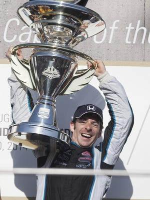 Simon Pagenaud lifts a 65 pound first place trophy after winning Saturday's inaugural Grand Prix of Indianapolis May 10, 2014 at the Indianapolis Motor Speedway.